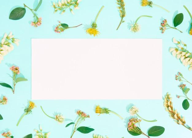 Carta bianca con fiori su sfondo blu. disposizione piatta, copia spazio, vista dall'alto.