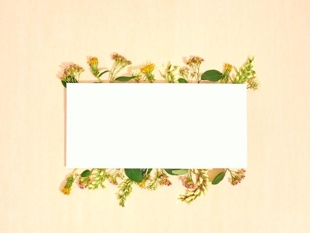 Carta bianca con cornice di fiori. disposizione piatta, copia spazio, vista dall'alto.
