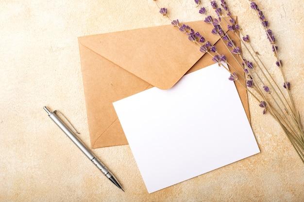 Carta bianca con busta kraft e fiori di lavanda su sfondo chiaro. cartolina pulita per le tue firme