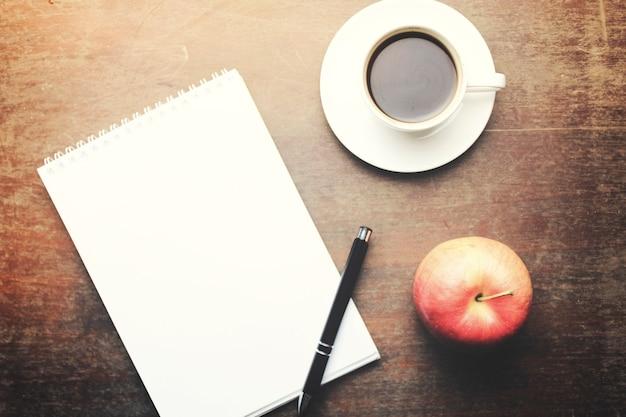 Carta bianca con penna, tazza di caffè e mela sul tavolo di legno