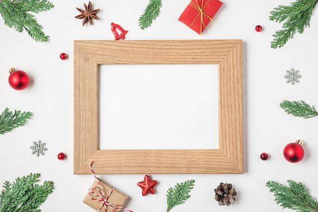 Carta fotografica in bianco in cornice fatta di decorazioni di scatole regalo di rami di abete