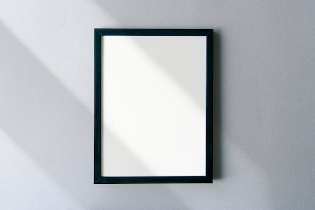 Mockup di cornice per foto vuota con ombre e luce solare sulla superficie. modello con spazio per il testo.