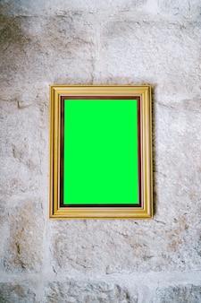 Foto vuota in cornice di legno appesa al muro di pietra