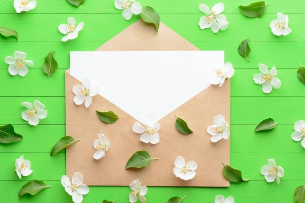 Un pezzo di carta bianco con una busta su fondo di legno verde