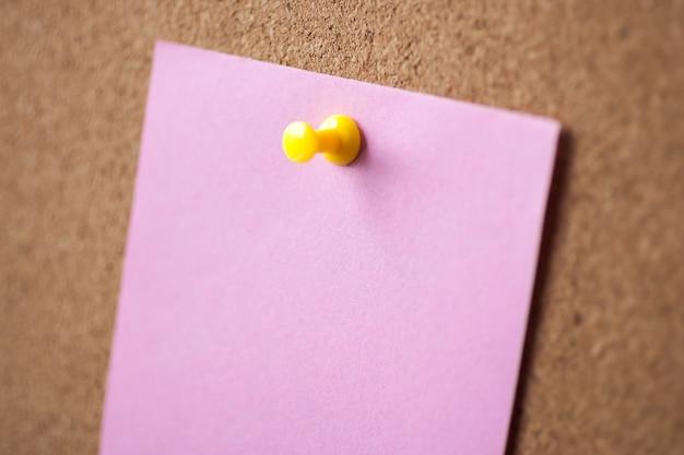 Perno di carta rosa in bianco sul fondo del bordo di sughero per ricordare.