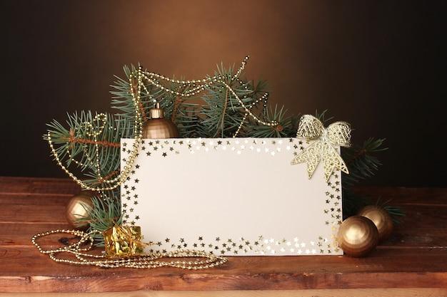 Cartolina in bianco, palle di natale e abete sul tavolo di legno su sfondo marrone