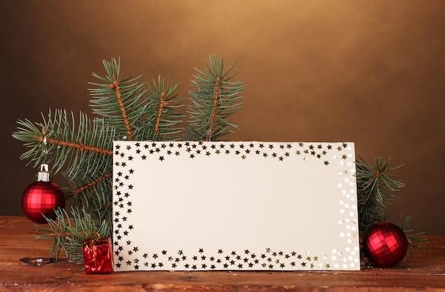 Cartolina in bianco, palle di natale e abete su tavola di legno su superficie marrone