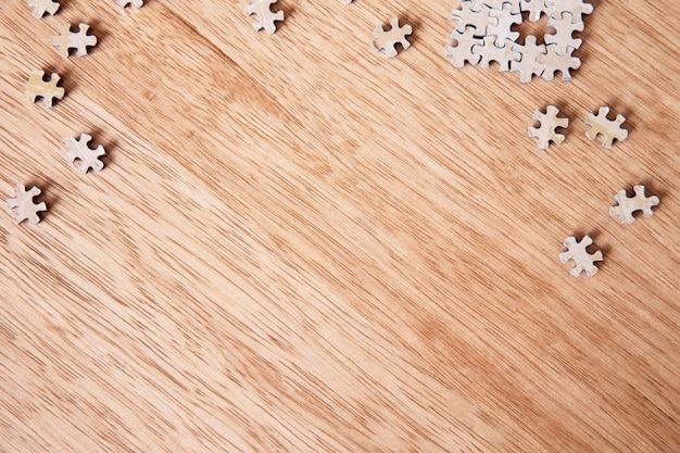 Pezzi di un puzzle in bianco sulla tavola di legno