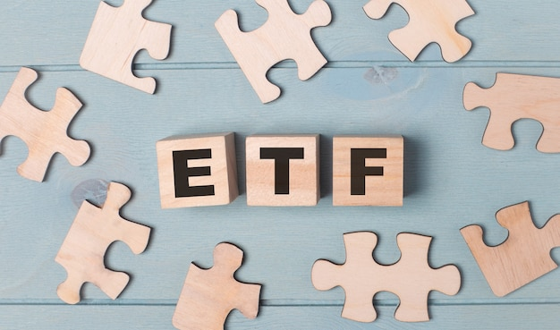 Puzzle vuoti e cubi di legno con gli etf exchange traded funds giacciono su uno sfondo azzurro.