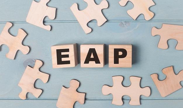 Puzzle vuoti e cubi di legno con il testo eap employee assistance program