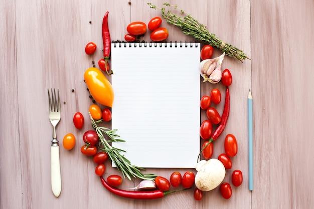 Libro di ricette in bianco. erbe aromatiche, pomodori e spezie fresche sulla tavola di legno