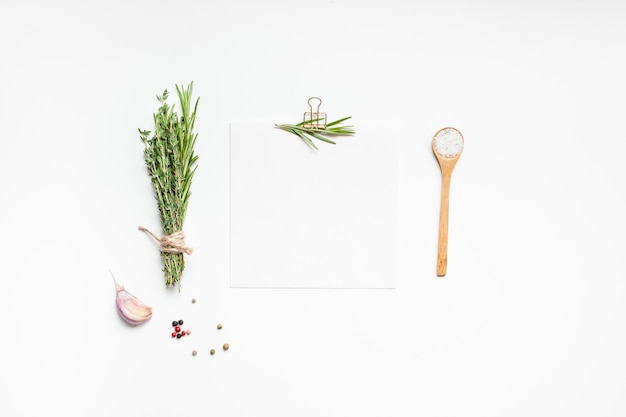 Pagina di carta bianca ricetta con clip, erbe verdi e spezie