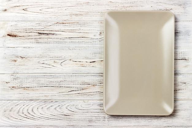 Piatto rettangolare bianco su legno. vista dall'alto