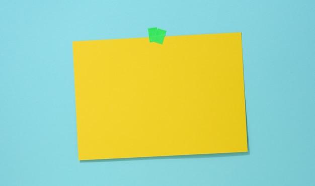 Foglio di carta giallo rettangolare vuoto incollato su uno sfondo blu. posto per un'iscrizione, annuncio