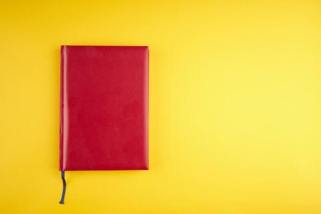 Diario in pelle rossa vuota su sfondo giallo alla moda. copia spazio. vista dall'alto