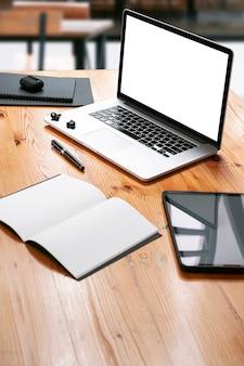 Computer portatile dello schermo in bianco e forniture sulla tavola di legno, vista veritcal.