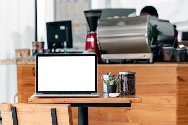 Computer portatile dello schermo in bianco sulla tavola di legno in caffetteria.