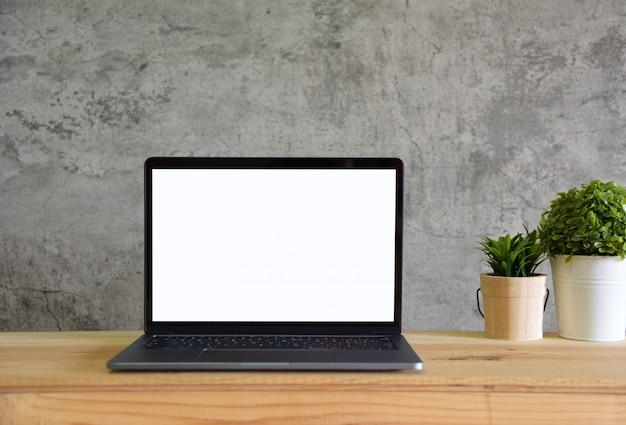 Computer portatile dello schermo in bianco sulla vista frontale del tavolo da lavoro nello stile della stanza del sottotetto