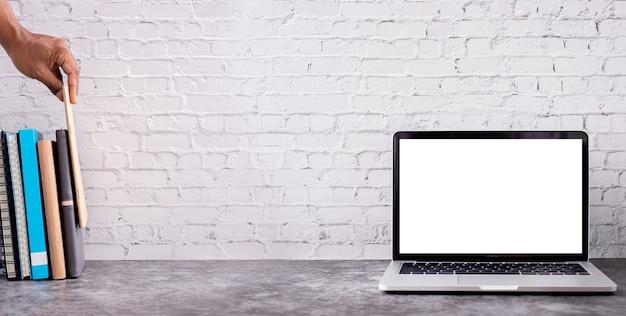 Schermo vuoto su laptop e mano umana che tiene libro sulla struttura del muro di mattoni.