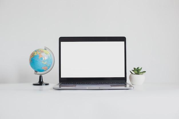 Computer portatile con schermo vuoto tra mini globo e succulento isolato su sfondo bianco
