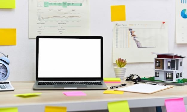 Mockup di laptop con schermo vuoto con appunti, modello di casa con forniture per ufficio sul tavolo e dati grafici sul muro, scrivania di design per la casa.