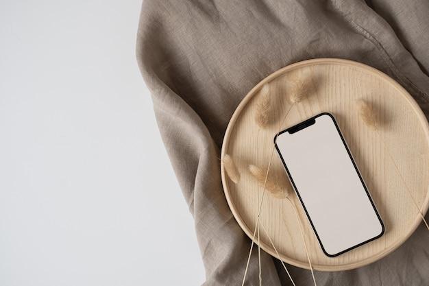 Telefono cellulare con schermo vuoto, erba di coda di coniglio su vassoio di legno con coperta di tela di lino stropicciata.