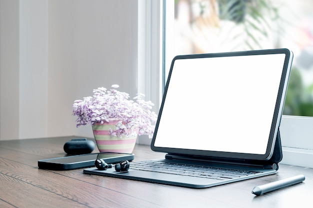 Tablet portatile a schermo vuoto con tastiera magica e gadget su tavolo di legno in soggiorno.