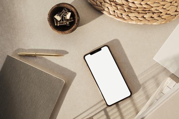 Smart phone con schermo vuoto, cancelleria su sfondo beige. area di lavoro della scrivania in stile home office.