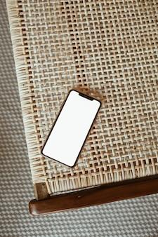 Smartphone con schermo vuoto sulla sedia in rattan. vista piana laico e dall'alto