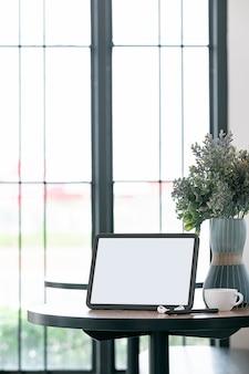 Tablet schermo vuoto, tazza di caffè e auricolare sul tavolino nella caffetteria, vista verticale.