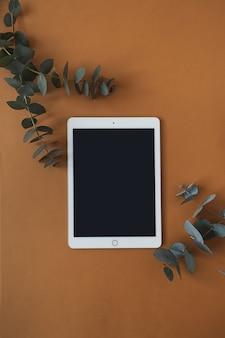 Pad tablet schermo vuoto con spazio vuoto copia, ramo di eucalipto secco su rosso intenso