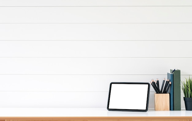 Compressa e rifornimenti dello schermo in bianco sulla tavola di legno bianca con la parete di legno bianca.