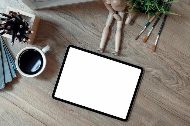 Tablet schermo vuoto e forniture sul tavolo di legno.