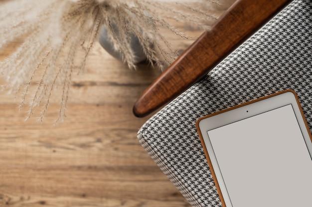 Tablet schermo vuoto sulla sedia vintage. blog minimalista, sito web piatto, vista dall'alto