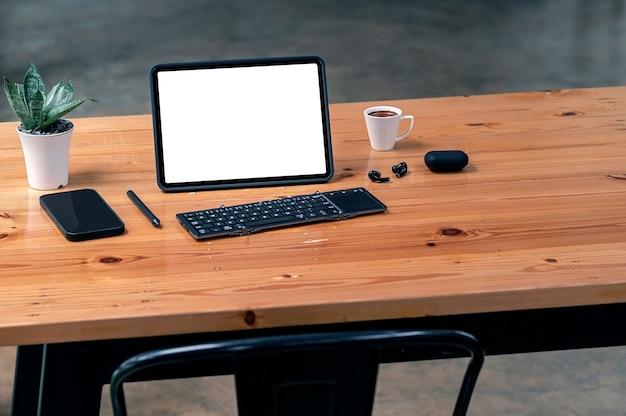 Tablet schermo vuoto con tastiera, smartphone e auricolare su tavolo in legno con spazio copia.