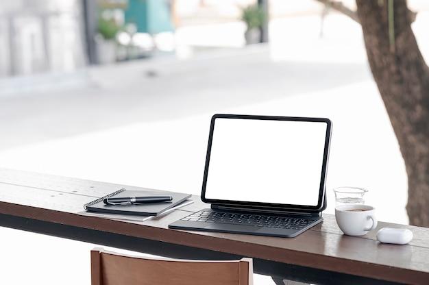 Tablet schermo vuoto con tastiera su bancone in legno tabel out side cafe.