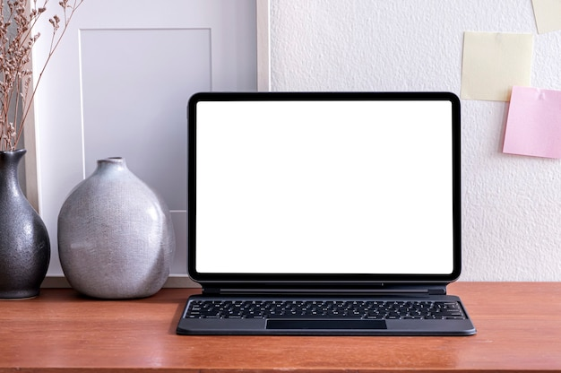 Tablet schermo vuoto con tastiera magica e vaso in ceramica sul tavolo di legno.