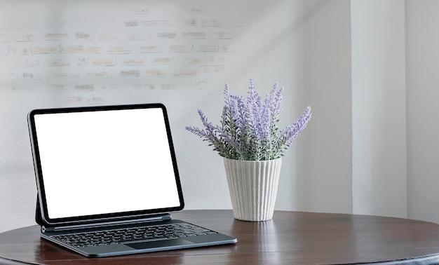 Tablet schermo vuoto con tastiera magica e fiore sul tavolo di legno nella stanza vuota.
