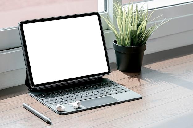 Tablet schermo vuoto con tastiera magica e gadget sul tavolo di legno nel soggiorno.