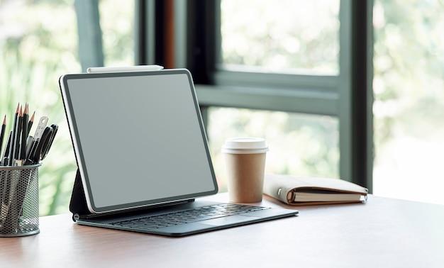Tablet schermo vuoto con tastiera magica e forniture sul tavolo di legno nella moderna stanza dell'ufficio.