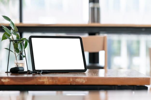 Tablet schermo vuoto sul tavolo di legno in co-workspace con copia spazio.