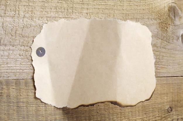 Foglio bianco di vecchia carta strappata su uno sfondo di legno