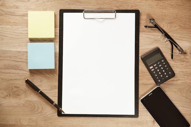 Un foglio di carta bianco una penna un telefono cellulare su un posto di lavoro dell'ufficio