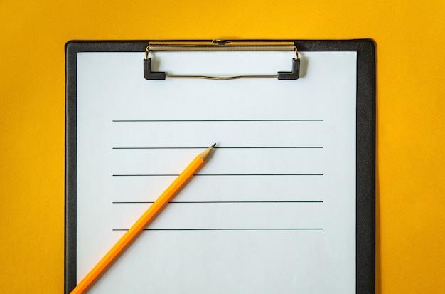 Foglio di carta bianco e una matita per scrivere sulla scrivania gialla