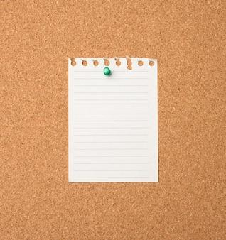 Foglio di carta bianco appuntato dal pulsante sul bordo di balsa marrone, copia dello spazio