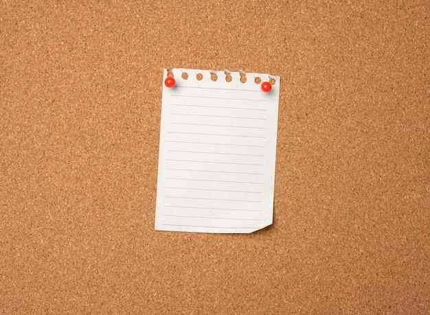 Foglio di carta bianco appuntato dal pulsante sulla bacheca di sughero marrone, copia dello spazio