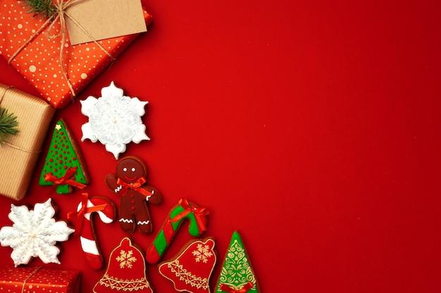 Foglio di carta bianco con regalo di natale e biscotti di panpepato su sfondo rosso