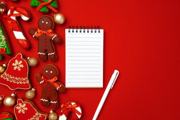 Foglio di carta bianco con biscotti di panpepato su sfondo rosso