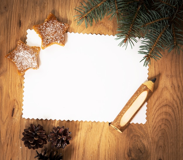 Foglio di carta bianco sul pavimento di legno con una matita e decorazioni natalizie
