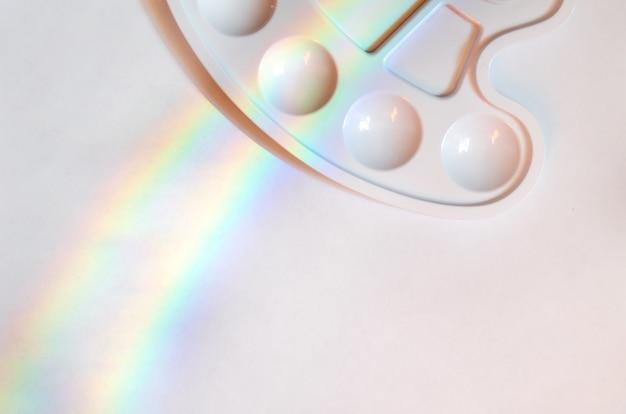 Foglio bianco di carta bianca con arcobaleno e tavolozza bianca vuota per mescolare le vernici.